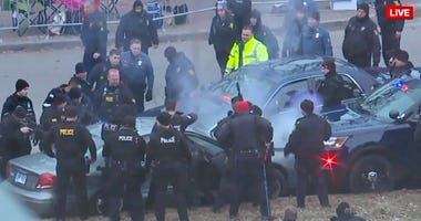 Police surround a car during the Chiefs' Super Bowl parade