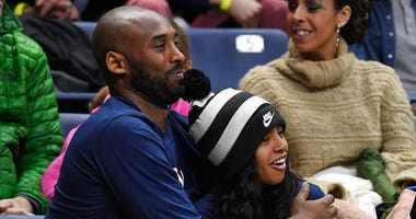 Kobe Bryant and his daughter Gianna watch the first half of an NCAA college basketball game between Connecticut and Houston in Storrs, Conn.