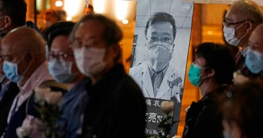 People wearing masks, attend a vigil for Chinese doctor Li Wenliang, in Hong Kong, Friday, Feb. 7, 2020.