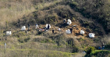 In this Tuesday, Jan. 28, 2020, file photo, investigators work at the scene of a helicopter crash that killed former NBA basketball player Kobe Bryant, his 13-year-old daughter, Gianna, and seven others, in Calabasas, Calif.