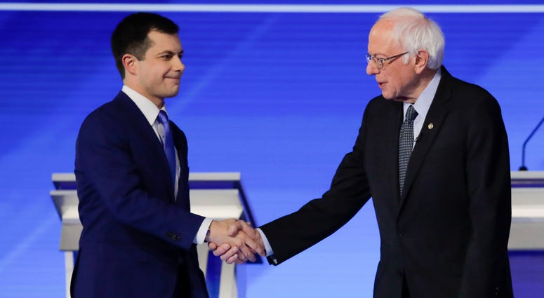 Democratic presidential candidates former South Bend Mayor Pete Buttigieg and Sen. Bernie Sanders shake hands on stage Friday, before the start of a Democratic presidential primary debate in Manchester, N.H.
