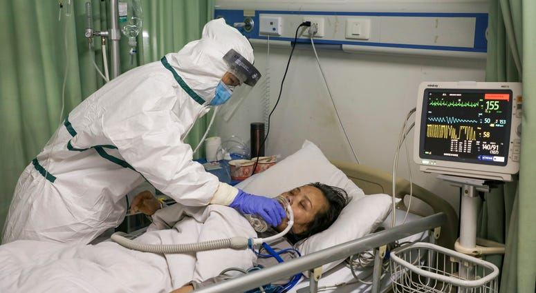 In this Thursday, Feb. 6, 2020, photo, a nurse feeds water to a patient in the isolation ward for 2019-nCoV patients at a hospital in Wuhan in central China's Hubei province.