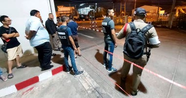 Police and bystanders stand near the scene of a shooting at the Terminal 21 mall, in Korat, Thailand, Saturday.