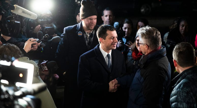 Democratic presidential candidate former South Bend, Ind., Mayor Pete Buttigieg meets with voters outside a polling place before they cast their ballots in a primary election, Tuesday, Feb. 11, 2020, in Manchester, N.H.