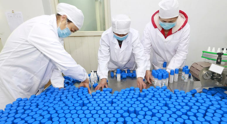 Workers pack bottles of alcohol disinfectant in a factory in Suining in southwest China's Sichuan province Tuesday, Feb. 11, 2020.
