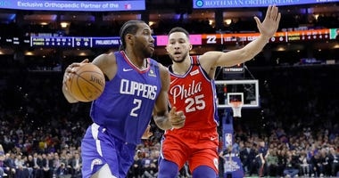 Los Angeles Clippers' Kawhi Leonard, left, drives past Philadelphia 76ers' Ben Simmons during the first half of an NBA basketball game, Tuesday, Feb. 11, 2020, in Philadelphia.