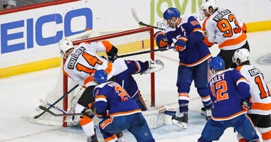 Philadelphia Flyers center Sean Couturier (14) scores a game-tying goal against New York Islanders goaltender Semyon Varlamov (40) during the third period of an NHL hockey game, Tuesday, Feb. 11, 2020, in New York.