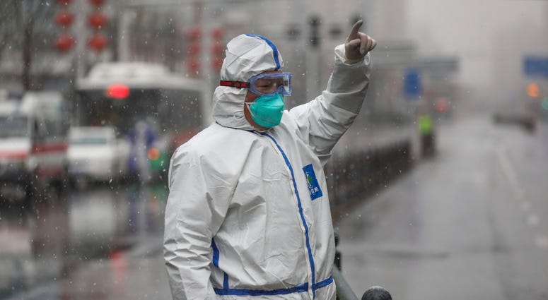 A worker wearing a protective suit gestures to a driver outside a tumor hospital newly designated to treat COVID-19 patients in Wuhan in central China's Hubei Province, Saturday, Feb. 15, 2020.