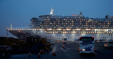 Buses arrive at a port as the Japan Self-Defense Forces prepare to move American passengers from the quarantined Diamond Princess cruise ship Sunday, Feb. 16, 2020, at Yokohama Port, near Tokyo.