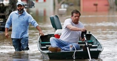 Marcus Morris steadies the boat as his neighbor Chris Sharp readies the trolling motor for another trip through their Pearl River flooded neighborhood in Jackson, Miss., Sunday, Feb. 16, 2020.
