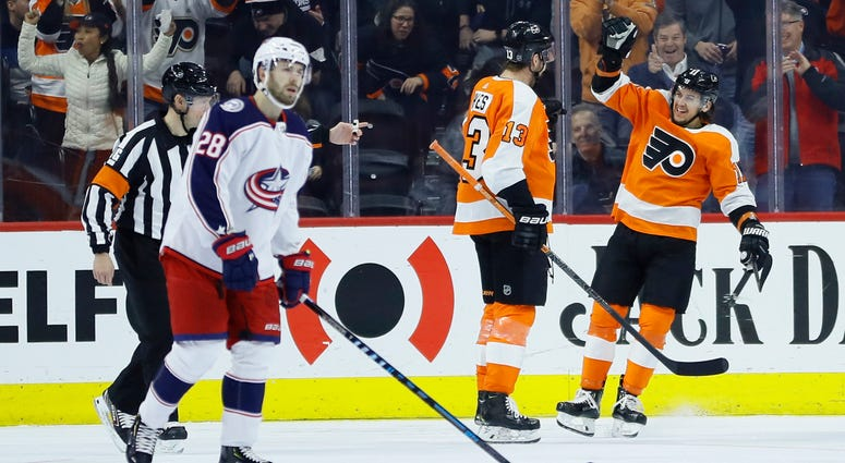 Philadelphia Flyers' Kevin Hayes (13) and Ivan Provorov (9) celebrate past Columbus Blue Jackets' Oliver Bjorkstrand (28) after a goal by Hayes during the first period of an NHL hockey game, Tuesday, Feb. 18, 2020, in Philadelphia.