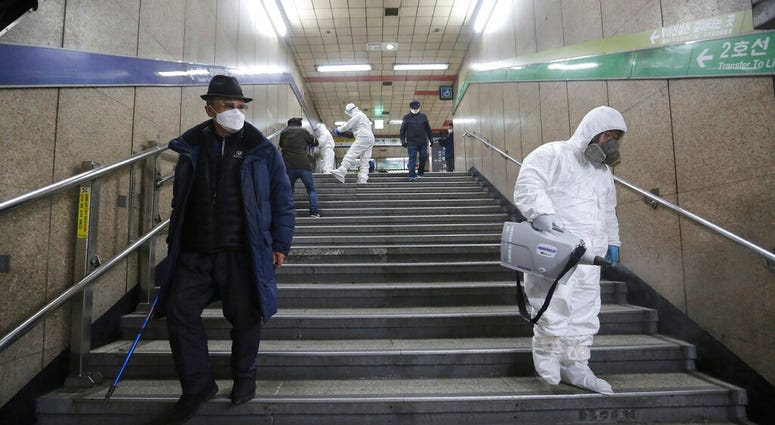 Workers wearing protective gears spray disinfectant as a precaution against the coronavirus at a subway station in Seoul, South Korea.