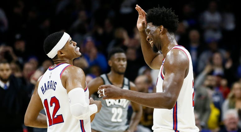 Philadelphia 76ers' Tobias Harris, left, and Joel Embiid celebrate during overtime in an NBA basketball game against the Brooklyn Nets, Thursday, Feb. 20, 2020, in Philadelphia. Philadelphia won 112-104.