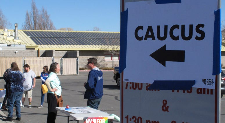 Volunteers for various campaigns talk to voters as they enter a presidential caucus site at Mendive Middle School in Sparks, Nev., on Saturday, Feb. 22, 2020.