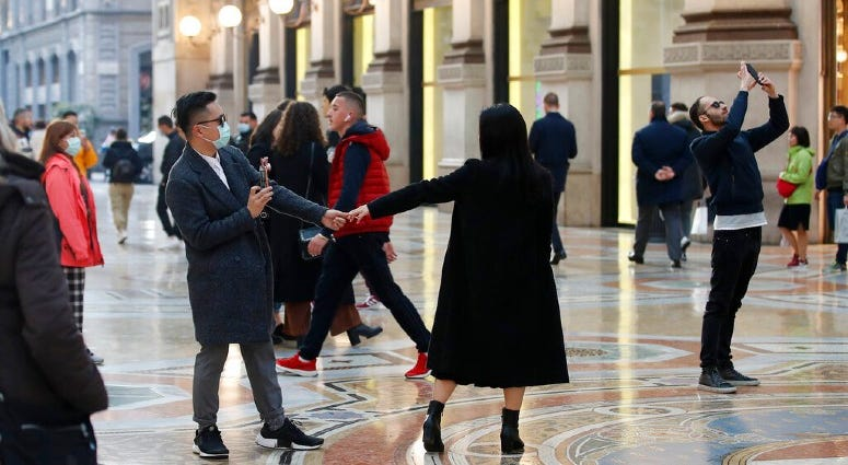 Tourists wearing sanitary masks move a few steps of dance, in downtown Milan, Italy, Sunday, Feb. 23, 2020.
