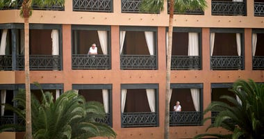 People stand at their balconies at the H10 Costa Adeje Palace hotel in Tenerife, Canary Island, Spain, Tuesday, Feb. 25, 2020.