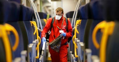 A cleaner sanitizes a wagon on a regional train, at the Garibaldi train station in Milan, Italy, Friday, Feb. 28, 2020.