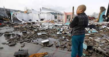Faith Patton looks over buildings destroyed by storms Tuesday, March 3, 2020, in Nashville, Tenn. Tornadoes ripped across Tennessee early Tuesday, shredding buildings and killing multiple people. Patton lives near the damaged area but her home was intact.