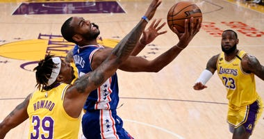 Philadelphia 76ers guard Alec Burks, center, shoots as Los Angeles Lakers center Dwight Howard, left, and forward LeBron James defend during the first half of an NBA basketball game Tuesday, March 3, 2020, in Los Angeles.