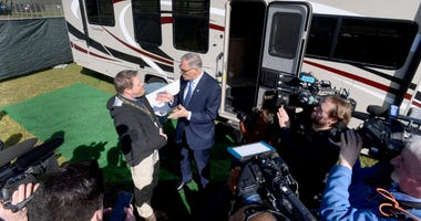 Washington Gov. Jay Inslee, joined by Nathan Weed, left, Dept. of Health incident commander, tours the group of RV's set-up for potential isolation and quarantine of COVID-19 patients in Grand Mound, Wash.