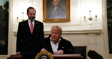 President Donald Trump signs an $8.3 billion bill to fight the coronavirus outbreak in the U.S., Friday, March 6, 2020 at the White House in Washington, as Department of Health and Human Services Secretary Alex Azar, looks on.