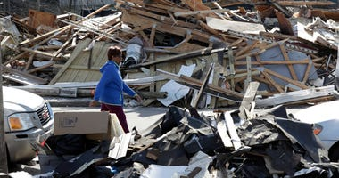 A woman walks down a street lined with debris Friday, March 6, 2020, in Nashville, Tenn.