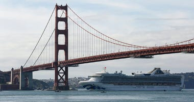 The Grand Princess cruise ship passes beneath the Golden Gate Bridge in this view from Sausalito, Calif.