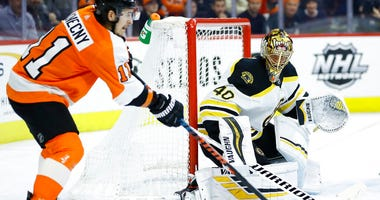 Philadelphia Flyers' Travis Konecny, left, passes the puck against Boston Bruins' Tuukka Rask during the second period of an NHL hockey game, Tuesday, March 10, 2020, in Philadelphia.