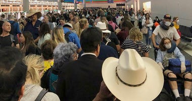 In this photo provided by Austin Boschen, people wait in line to go through the customs at Dallas Fort Worth International Airport in Grapevine, Texas, Saturday, March 14, 2020.