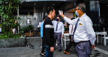 a man scans a visitor's forehead to check his temperature before entering the Asia Square Tower in Singapore.