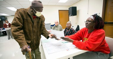 Henry Williams receives his ballot from first time election judge Kimberly Sims at United Faith Baptist Church in Rockford, Ill., Tuesday, March 17, 2020.