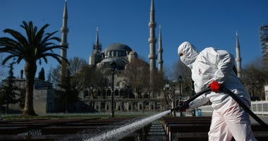 A municipality worker wearing a face mask and protective suits disinfects chairs outside the the historical Sultan Ahmed Mosque, also known as Blue Mosque, amid the coronavirus outbreak, in Istanbul, Saturday, March 21, 2020.