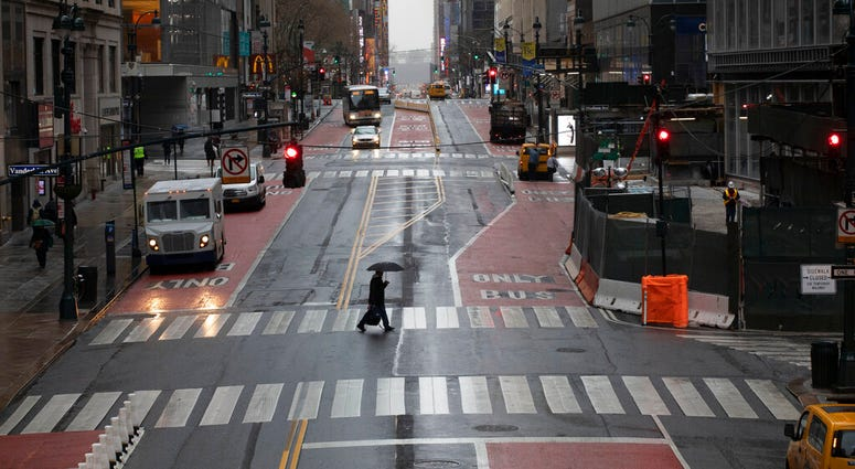 A commuter crosses 42nd Street in front of Grand Central Terminal during morning rush hour, Monday, March 23, 2020, in New York. Gov. Andrew Cuomo has ordered most New Yorkers to stay home from work to slow the coronavirus pandemic.