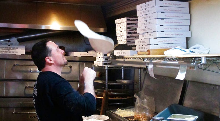 In this March 24, 2020, photo, Michael Morin, co-owner of Federico's Pizza in Belmar N.J., makes a pizza