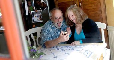Seen through their kitchen window, Allan and Debbie Cameron contact their grandchildren via the internet Wednesday, March 25, 2020, in Chandler, Ariz.