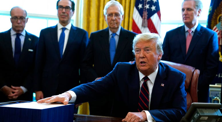 President Donald Trump speaks before he signs the coronavirus stimulus relief package in the Oval Office at the White House, Friday, March 27, 2020, in Washington.