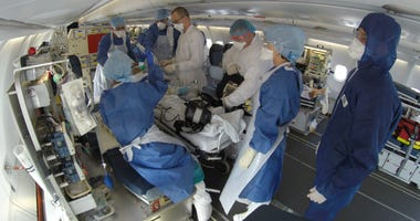 This GoPro image provided Saturday, by the French Army shows doctors taking care of evacuated patients infected with the COVID-19 disease, aboard a military plane from Mulhouse, eastern France to Bordeaux, southwestern France, Friday.