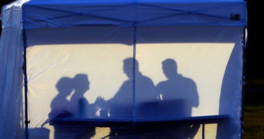 FILE - In this Wednesday, March 25, 2020 file photo, medical personnel are silhouetted against the back of a tent before the start of coronavirus testing in the parking lot outside of Raymond James Stadium in Tampa, Fla.