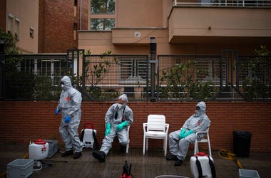 Firefighters wearing protective suits wait outside a nursing home before disinfecting it in efforts to prevent the spread of the new coronavirus in Barcelona, Spain, Monday, March 30, 2020.