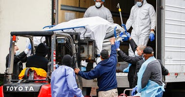 A body rapped in plastic is unloaded from a refrigerated truck and handled by medical workers wearing personal protective equipment due to COVID-19 concerns, Tuesday, March 31, 2020, at Brooklyn Hospital Center in the Brooklyn borough of New York.