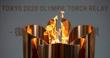 In this March 24, 2020, file photo, the Olympic Flame burns during a ceremony in Fukushima City, Japan.
