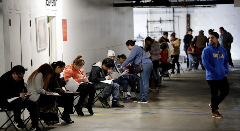 Unionized hospitality workers wait in line in a basement garage to apply for unemployment benefits at the Hospitality Training Academy in Los Angeles.