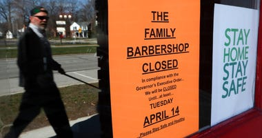 A pedestrian walks by The Family Barbershop, closed due to a Gov. Gretchen Whitmer executive order, in Grosse Pointe Woods, Mich., Thursday, April 2, 2020.