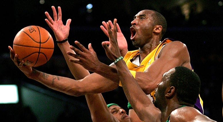 In this Feb. 23, 2007, file photo, Los Angeles Lakers' Kobe Bryant, top, goes up for a shot between Boston Celtics' Paul Pierce, left, and Al Jefferson during the first half of an NBA basketball game in Los Angeles.