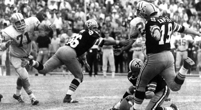 New Orleans Saints' Tom Dempsey (19) moves up to kick a 63-yard field goal as teammate Joe Scarpati holds the ball and Detroit Lions' Alex Karras (71) rushes in while Saints' Bill Cody (66) blocks, in New Orleans.