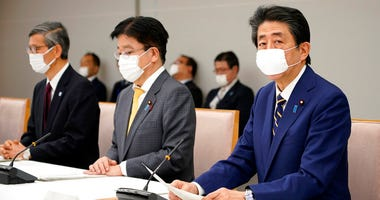 Japanese Prime Minister Shinzo Abe, right, declares a state of emergency during a meeting of the task force against the coronavirus at the his official residence in Tokyo, Tuesday, April 7, 2020.