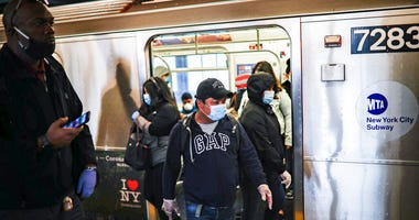 Subway riders, wearing personal protective equipment due to COVID-19 concerns, step off a train, Tuesday, April 7, 2020, in New York.