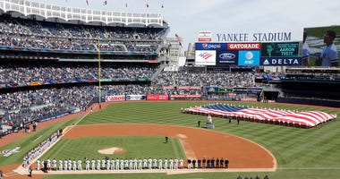 In this March 28, 2019, file photo, a large flag is unfurled during the national anthem before an opening day baseball game between the New York Yankees and the Baltimore Orioles at Yankee Stadium in New York.