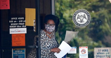 A masked worker at this state WIN job center in Pearl, Miss., holds an unemployment benefit application form as she waits for a client, Tuesday, April 21, 2020.