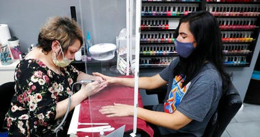 Manicurist Rhonda Simpson, left, polishes nails for her customer Faith at the reopened Salon A la Mode in Dallas, Friday, April 24, 2020.